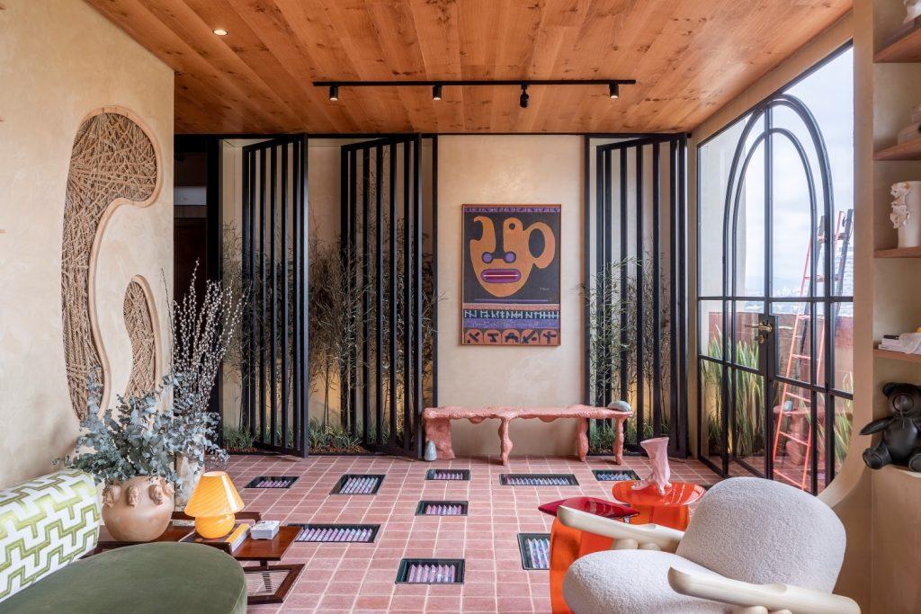 Living Galeria: Ambiente com revestimento de madeira no teto e demais paredes em tom nude, elementos vazados na parede, janela grande com detalhes na estrutura de ferro, piso de cerâmica, sofá verde, poltrona branca, mesinhas de centro laranjas e prateleiras com muitos objetos
