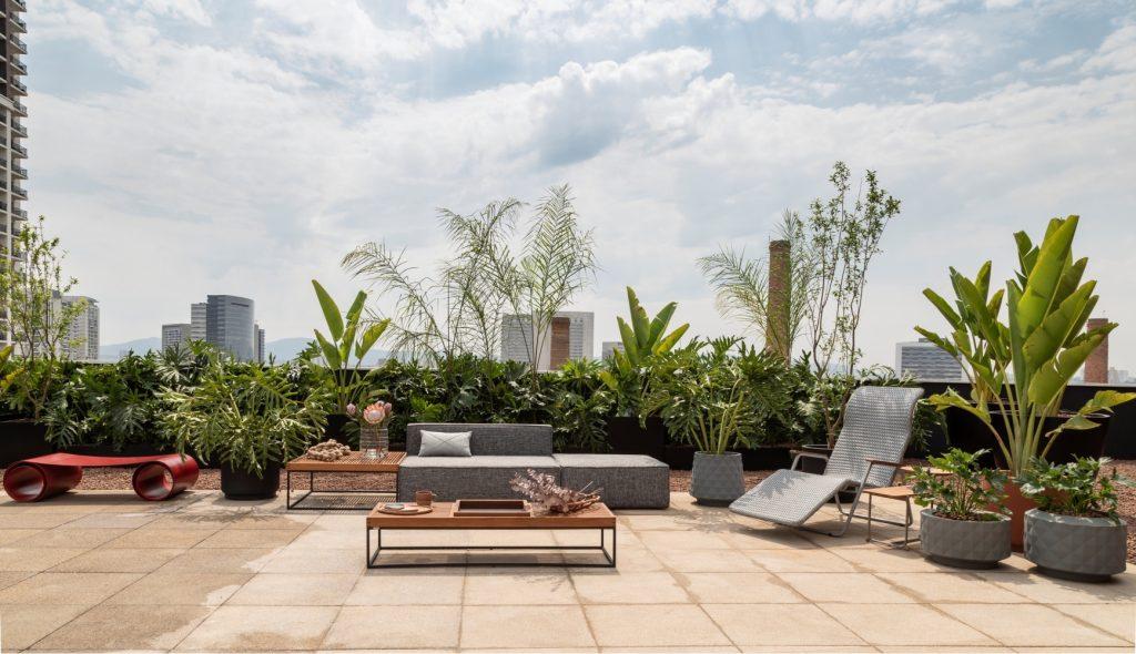 Area externa a céu aberto, com sofá cinza, piso com placas de concreto, espreguiçadeira cinza, mesinha de centro de madeira, banco vermelho e diversos vasos de plantas